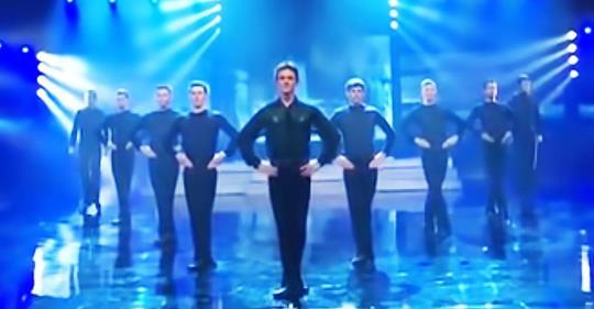 9 Männer reihen sich zum Tanzen auf, aber achte auf den Mann vorne, wenn die Frau mit der Trommel auf die Bühne kommt