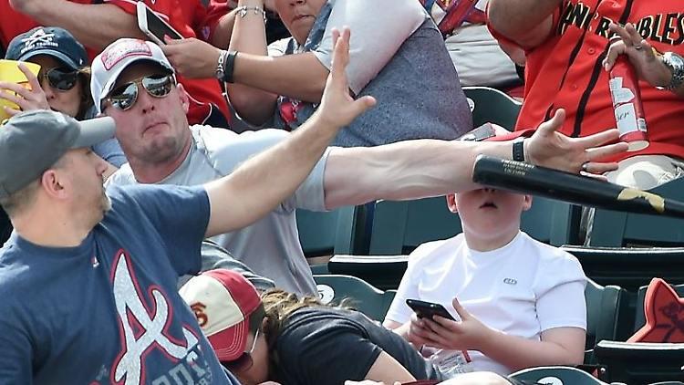 Vater beschützt seinen Sohn, als ein Baseball Schläger auf die Tribüne fliegt