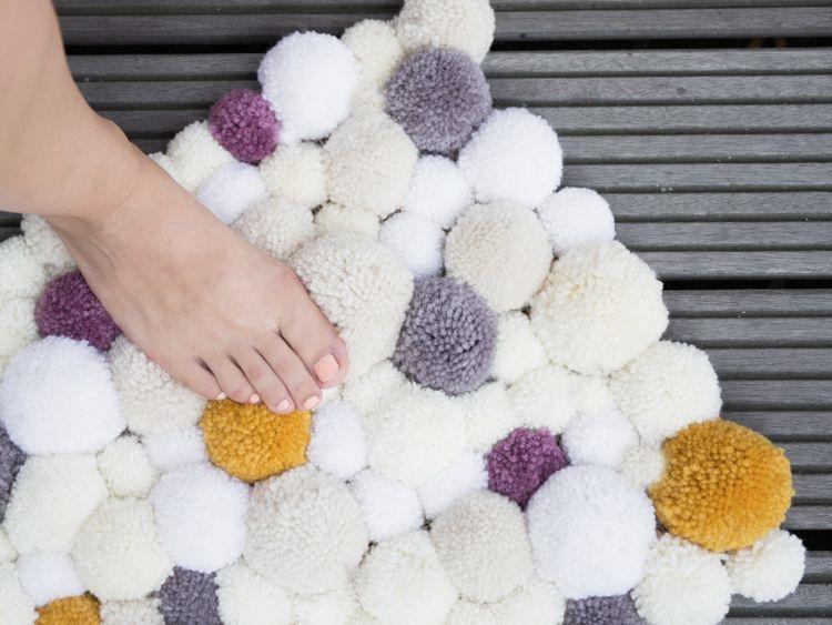 Flauschig: Bastle aus Klopapierrollen und Wolle einen Bommelteppich.
