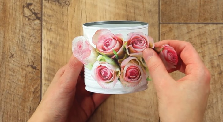 Sie klebt einen Zeitschriftausschnitt auf eine Konservendose: hier ein entzückender Gegenstand, der durchs Recyclen entsteht