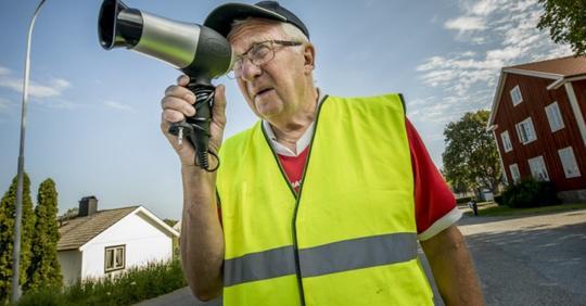 Alter Mann benutzt einen Haarföhn als Radargerät, um die Autos, die zu schnell unterwegs sind, langsamer fahren zu lassen