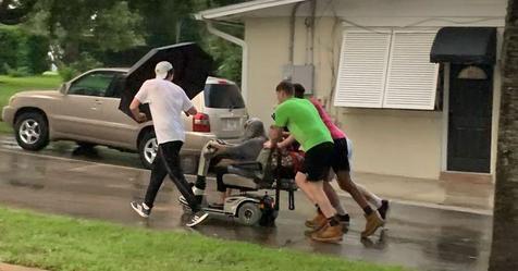 Männer schieben ältere Frau auf kaputten Rollstuhl im strömendem Regen nach Hause
